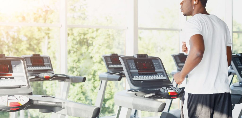 African-american man running on treadmill in gym, jogging in fitness club, listen mobile music. Healthy lifestyle concept, cardio training, back view, copy space